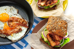 Fried eggs with bacon in cast iron pan and burgers-like sandwiches stock photography
