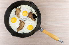 Fried eggs and bacon in cast iron skillet on table Royalty Free Stock Images