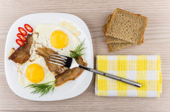 Fried eggs and bacon with dill, chili peppers, garlic Royalty Free Stock Photos