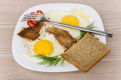 Fried eggs and bacon with dill, peppers, garlic in plate Stock Photo