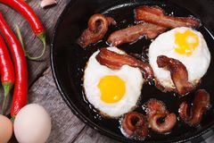 Fried eggs with bacon in a frying pan. top view Royalty Free Stock Image