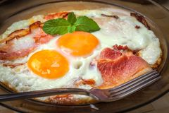 Fried eggs with bacon. Fried eggs with bacon on a glass plate royalty free stock photography