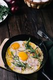 Fried eggs with bacon and greenery royalty free stock images