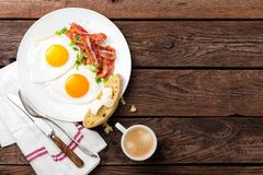 Fried eggs, bacon and italian ciabatta bread on white plate. Cup of coffee. Breakfast. Top view. Wooden background. Fried eggs, bacon and italian ciabatta bread royalty free stock image