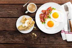 Fried eggs, bacon and italian ciabatta bread on white plate. Cup of coffee. Breakfast. Top view. Wooden background royalty free stock photography