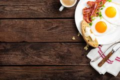 Fried eggs, bacon and italian ciabatta bread on white plate. Cup of coffee. Breakfast. Top view. Wooden background royalty free stock images