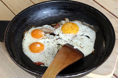 Fried eggs with bacon on the pan -  hearty breakfast Stock Image