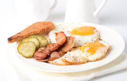 Fried eggs with bacon, pickles on the plate of toast on a white background. Fried eggs with bacon and toast on white background Stock Images