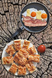 Fried Eggs and Bacon Rashers in Teflon Frying Pan with Tomato and Plateful of Gibanica Cheese Pie Slices Set on Old Cracked Stump Royalty Free Stock Photography