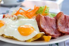 Fried eggs with bacon and salad Stock Image