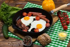 Fried eggs with bacon and sausages in a frying pan royalty free stock photography