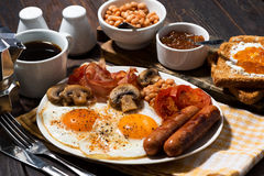 Fried eggs with bacon, sausages and vegetables for breakfast Stock Photography