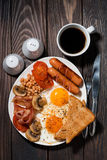 Fried eggs with bacon, sausages and vegetables for breakfast Royalty Free Stock Images