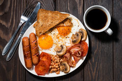 Fried eggs with bacon, sausages and vegetables for breakfast Stock Image