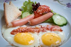 Fried eggs with beef and sausages . Royalty Free Stock Photography