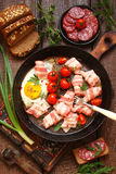 Fried eggs, bacon, smoked meat, sausage, vegetables and herbs, a Stock Images