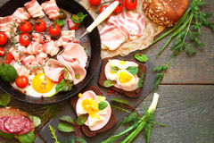 Fried eggs, bacon, smoked meat, sausage, vegetables and herbs, a Stock Photography