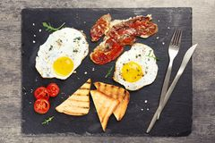 Fried eggs, bacon and toasts Stock Photography