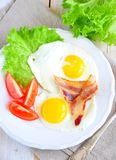 Fried eggs with bacon and tomato slice on a white plate Royalty Free Stock Photography