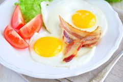 Fried eggs with bacon and tomato slice on a white plate Stock Photography