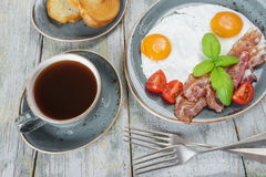 Fried eggs,  bacon, tomato, toast and a cup of coffee Stock Image