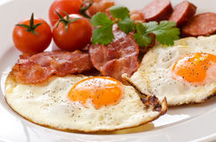 Fried eggs with bacon and tomatoes royalty free stock photos