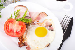 Fried eggs with bacon and tomatoes Stock Photo