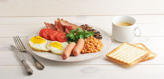 Fried eggs with bacon, tomatoes, beans, mushrooms and sausages i Royalty Free Stock Photo