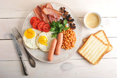 Fried eggs with bacon, tomatoes, beans, mushrooms and sausages i Royalty Free Stock Photos
