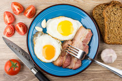 Fried eggs with bacon, tomatoes, garlic and bread on table Royalty Free Stock Images