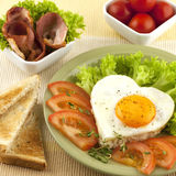 Fried eggs with bacon and tomatoes Royalty Free Stock Photo