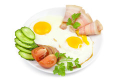 Fried eggs with bacon and vegetables Stock Photography