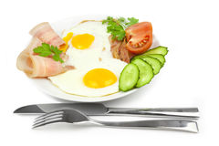 Fried eggs with bacon and vegetables Stock Images