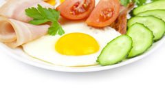 Fried eggs with bacon and vegetables Royalty Free Stock Images
