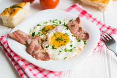 Fried eggs with bacon on white background Royalty Free Stock Photos