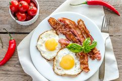 Fried eggs with bacon on the wooden table Royalty Free Stock Images