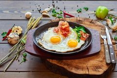 Fried eggs with beacon on a stone plate. With a wooden background and pepper on the table stock photos