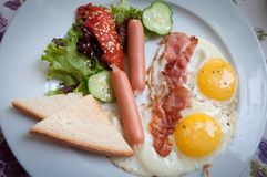 Fried eggs with beef and sausages . Royalty Free Stock Image