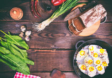 Fried eggs in a black frying pan, near bread and fresh vegetable Royalty Free Stock Image