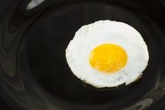 Fried eggs. On a black plate closeup Stock Photo