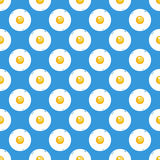 Fried eggs on blue background seamless pattern. Royalty Free Stock Images