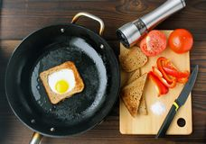 Fried eggs in bread in a pan with cut vegetables on the table. stock photos