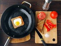 Fried eggs in bread in a pan with cut vegetables on the table. stock photography