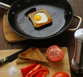 Fried eggs in bread in a pan with cut vegetables on the table. stock photo