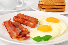 Fried eggs for breakfast. Fried eggs, bacon and sausages for breakfast stock photos