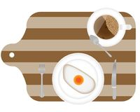 Fried eggs for breakfast on plate, with fork and knife on the wooden cooked desk. Top view Royalty Free Stock Photo