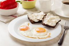 Fried eggs for breakfast. Traditional breakfast with fried eggs, bread with cream cheese and coffee. Selective focus Royalty Free Stock Image