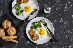 Fried eggs, broccoli, chicken meatballs, homemade whole wheat bread - tasty simple dinner. On a dark background Royalty Free Stock Photos