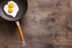 Fried eggs on a brown wooden background. Two fried eggs in a cast iron skillet on a brown wooden background Stock Image