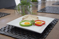 Fried Eggs. In capsicum/peppers rings on a white plate Royalty Free Stock Images